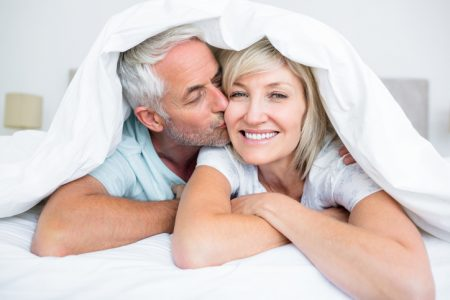 Closeup of mature man kissing womans cheek in bed