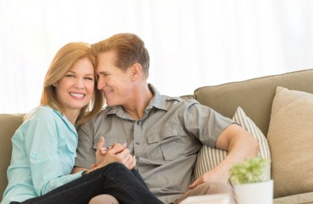 Loving mature couple sitting on sofa at home