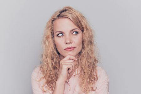 Portrait of young attractive nice cute caucasian shy curly-haired blonde girl wearing formal shirt, thinking, touching her chin with fingers. Isolated over grey background
