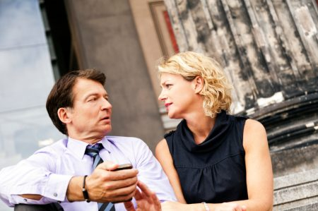 Mature Couple Sitting on Steps with Smart Phone